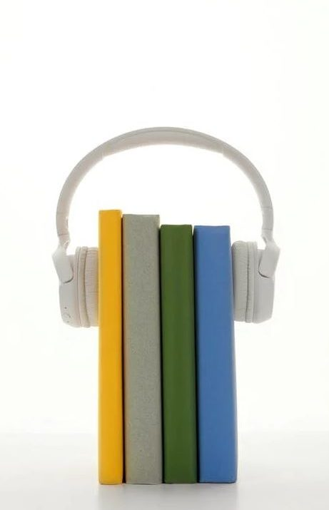 vertical line of colored notebooks held upright with white headphones