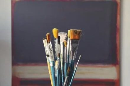 bundle of paintbrushes in front of chalkboard